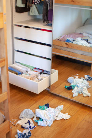 Vertical storage of clothing. Clothing folded for vertical storage in the linen drawer. Preparing. Sliding wardrobe. Room interior. Neatly folded clothes in chest of drawers. Newborn. Zdjęcie Seryjne