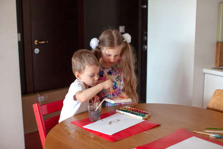 Seven year old girl and three year old boy paint in the kitchen. Modern home interior with white color. Brother and sister spend time together.