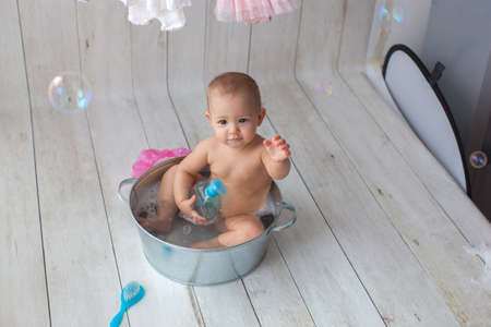 Cute baby girl takes a bath. Basin on wooden backgroun. Clothes are dried on a hanger. Bottom view.