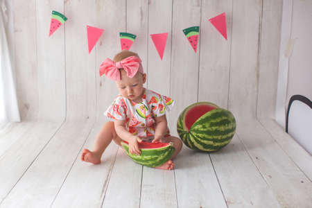 One year old baby girl eating watermelon. Paper flag garland on background. Archivio Fotografico