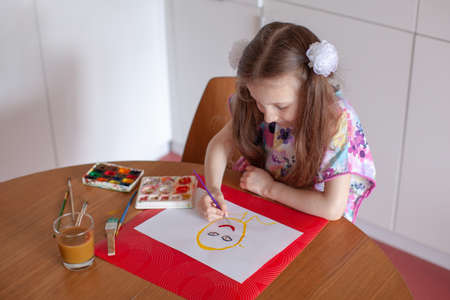 7 years old girl painting with watercolor in the kitchen. Home interior. Stock Photo