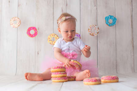 One year old baby girl celebrates her birthday. Doughnut background. Handmade paper cutout garland.