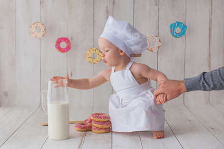 One year old baby girl celebrates her birthday. Doughnut background. Handmade paper cutout garland. Girl reaches for a carafe of milk. Dad holds her hand. Archivio Fotografico