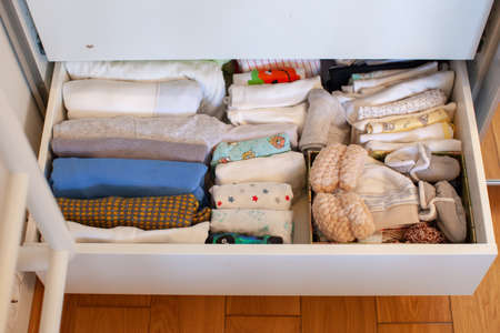 Vertical storage of clothing. Clothing folded for vertical storage in the linen drawer. Nursery. Sliding wardrobe. Room interior. Neatly folded clothes in chest of drawers. Newborn baby clothes.