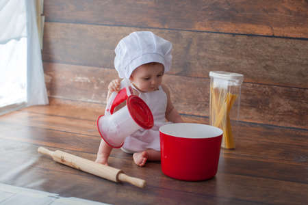 Little chef in apron and a suit of a cook, sits on a dark wooden background. Chefs hat on her head. She is a bakery. 免版税图像
