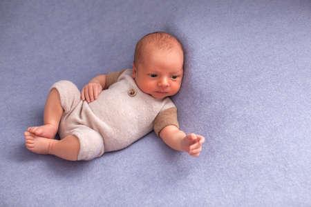 蓝色纺织品背景的新出生的男婴。13天大。西装。