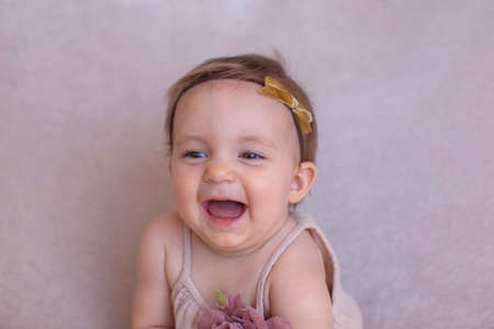 Portrait of a one year old girl, purple background. The bezel on her head. Smile.