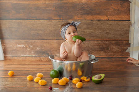 One year old baby girl takes a bath with apricots. She eats avocado. Dark wooden background.