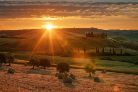 Magnificent spring landscape at sunrise.Beautiful view of typical tuscan farm house, green wave hills, cypresses trees, hay bales, olive trees, beautiful golden fields and meadows.Tuscany, Italy.