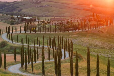 Magnificent rural landscape at sunset. Stunning view of typical tuscan farm house, green wave hills, cypresses trees, beautiful golden fields and meadows.Tuscany, Italy, Europe