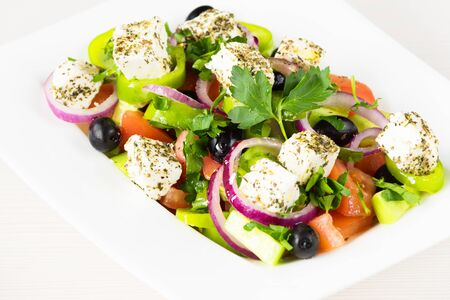 Greek salad with fresh tomato, cucumber, red onion, basil, feta cheese, black olives, Italian herbs and olive oil in white dish on white wooden table.