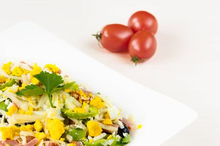 Traditional Bulgarian Shepherd salad with tomatoes, peppers, cucumbers, mushrooms, ham, cheese and eggs in white dish on white wooden table. Bulgarian cuisine, Balkan culture