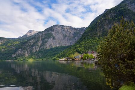 Scenic picture-postcard view of traditional old wooden houses in famous Hallstatt mountain village at Hallstattersee lake in the Austrian Alps in summer, region of Salzkammergut, Austria