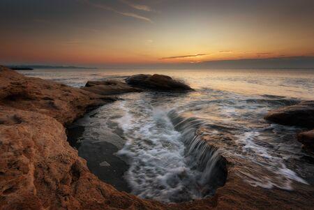 Seascape during sunrise. Beautiful natural seascape, blue hour. Sea sunrise at the Black Sea coast. Magnificent sunrise with clouds and fire sun in the middle of December.Ravda, Bulgaria 免版税图像