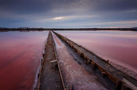 Beautiful landscape on sunset with a salt farm. Magnificent colors, dark clouds. Burgas, Bulgaria. 免版税图像