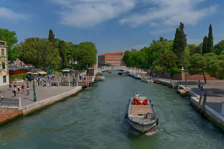 VENICE, ITALY MAY 23, 2017: Traditional narrow canal street with gondolas and old houses in Venice, Italy. Architecture and landmarks of Venice. Beautiful Venice postcard.