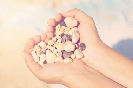 Close-up shot of hands with stones on a pebble beach background. Concept of summer holidays at sea, Zakynthos Island, Greece. 免版税图像
