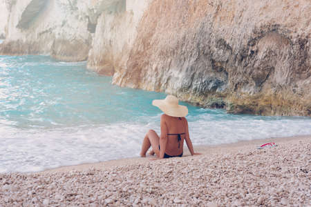 Young beautiful woman in swimsuit and hat relaxing on Navagio beach, Zakynthos island, Greece