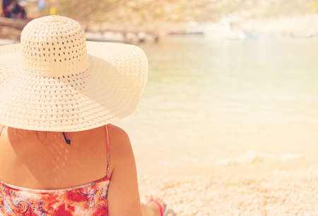 Young woman in summer dress and hat standing on sand and looking to a the port of Porto Vromi, Greece.