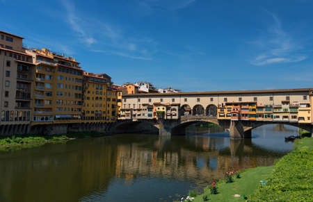 FLORENCE, ITALY Y 25, 2017: River Arno and famous bridge Ponte Vecchio (The Old Bridge) at sunny summer day. Florence, Tuscany, Italy