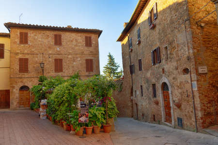 PIENZA, ITALY - MAY 26, 2017: Beautiful narrow street with sunlight and flowers in the small magical and old village of Pienza, Val D'Orcia Tuscany, Italy. 新闻类图片