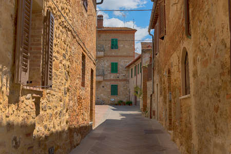 Beautiful narrow street with sunlight and flowers in the small magical and old village of Pienza, Val D'Orcia Tuscany, Italy