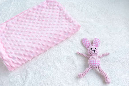 Pink blanket for baby girl and toy on a white fur carpet. Newborn Baby Concept. Baby Girl Clothes Set.