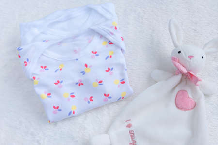 Bodysuits for baby girl and a toy on a white fur carpet. Newborn Baby Concept. Baby Girl Clothes Set.