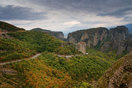 Beautiful scenic view, Orthodox Monastery of Rousanou (St. Barbara), immense monolithic pillar, green and yellow foliage at the background of stone wall in Meteora, Pindos Mountains, Thessaly, Greece.
