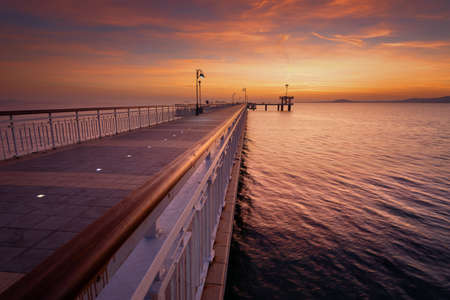 Dramatic sunrise on the beach in Burgas, Bulgaria. Sunrise on the Burgas Bridge. Bridge in Burgas - symbol of the city.
