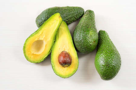 Close-up photo of avocados cut to half, brown seeds visible, with more avocados on white wooden background. Fresh sliced avocado.Vegetarian food concept.