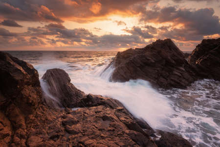 Sea waves hit the rock during magnificent sunrise with clouds and sun at the beginning of September. Rezovo village, Bulgaria 免版税图像