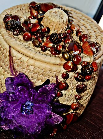 Rattan basket withbrown necklet and flower