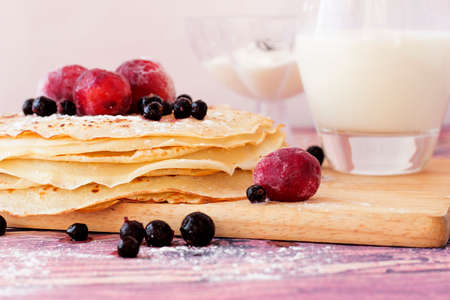 Pancakes with black currant and plum on wooden plate closeup.