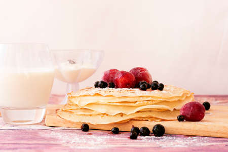 Stack of kefir (buttermilk) pancakes with black currant, plum, milk and sourcream. Traditional food for Russian pancake week. Standard-Bild