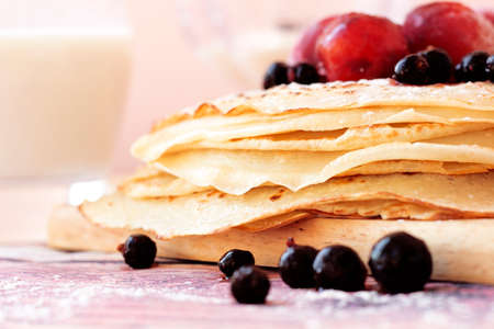 Buttermilk pancakes with black currant and plum on wooden plate closeup.