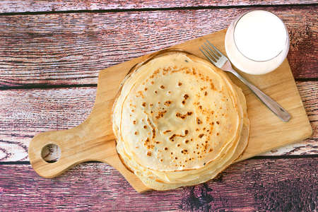 Stack of fresh russian pancakes. Pancakes with milk on wooden background. Top view. 版權商用圖片