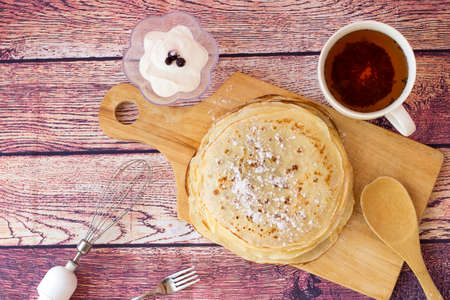 Breakfast with pancakes and tea. Kefir pancakes on wooden background.Top view.