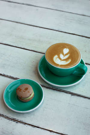 Cup of cappuccino on white wooden background. Green cup and delicious dessert. Side view.