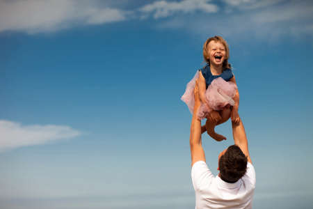 Father throwing up his smiling daughter in the blue sky. Happy moments in a babygirl childhood. Happy family playing together. Slow motion. 写真素材 - 143278139
