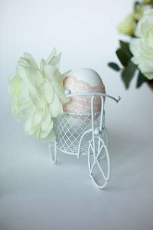 Rustic Easter composition with egg decorated ribbon lace, white little bicycle with fabulous ranunculus and flowers composition. Side view.