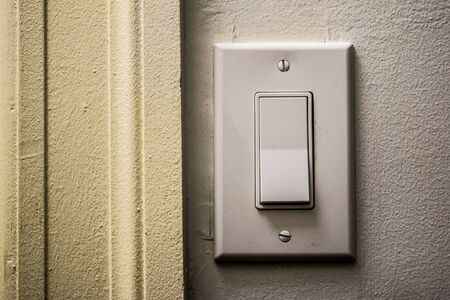 energy use: A light switch with stark shadows perhaps showing the darker side of energy use. Stock Photo