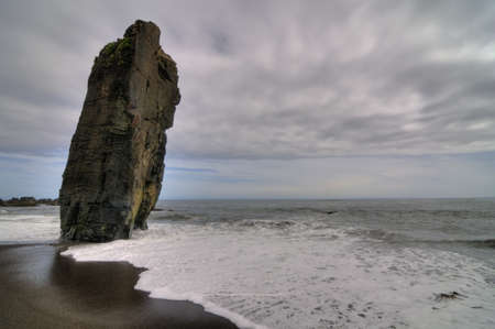 inclined: Lonely beach with a big inclined rock