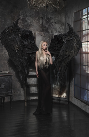 Beautiful blond woman in black dress with black wings