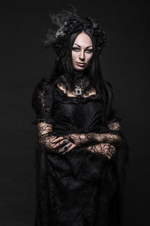 Portrait of beautiful Gothic woman in dark dress in studio
