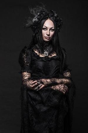 Portrait of beautiful Gothic woman in dark dress in studio