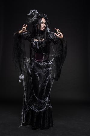 gothic fetish: Portrait of beautiful Gothic woman in dark dress in studio