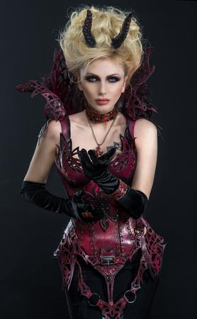 스튜디오에서 어두운 섹시 드레스에서 아름 다운 악마 여자의 초상화