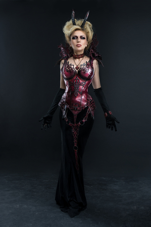 gothic fetish: Portrait of beautiful devil woman in dark sexy dress in studio