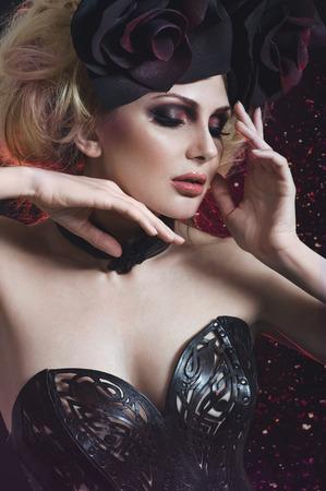 gothic fetish: Portrait of beautiful blond woman in dark sexy corset in studio